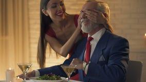 Vrij jonge dame sluitende ogen van het oude heer wachten in restaurant, verrassing stock videobeelden