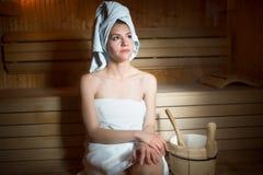 Vrij jonge die vrouwenzitting in een houten sauna wordt ontspannen Jonge vrouw in witte handdoekzitting in Finse sauna Royalty-vrije Stock Afbeeldingen