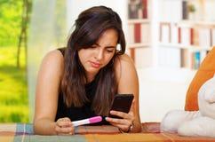 Vrij jonge donkerbruine vrouw het liggen het huistest die van de holdingszwangerschap bij het mobiele scherm staren, die emotione Stock Foto
