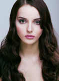 Vrij jonge donkerbruine vrouw met haarstijl zoals de leuke golven van het poppenkapsel, betoverende make-up royalty-vrije stock foto