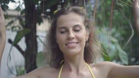 Vrij jonge gelukkige vrouw die bikini dragen die door klimplanten lopen en tijdens haar vakantie in langzame motie glimlachen stock video
