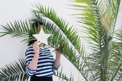 Vrij jonge Kaukasische vrouw in het gestripte vest verbergen achter witte LEIDENE gloeiende ster en groene palmbladen stock foto's