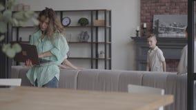 Vrij jonge laptop die van de moederholding door celtelefoon proberen te spreken terwijl haar vier tienerzonen die araund het spel stock video