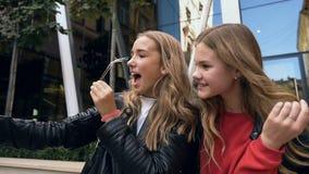 Vrij jonge meisjes die grappige gezichten maken en voor selfiefoto glimlachen op smartphone outdoors Vriendschap, levensstijl stock videobeelden