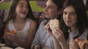 Vrij jonge meisjes die pizza eten en een pret in koffie fuving 4K stock video
