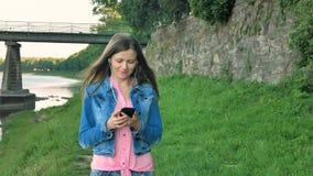 Vrij jonge meisjesgangen langs de waterkant die smartphone met oortelefoons gebruiken Brug en uitstekende muur van wilde steen bi stock video