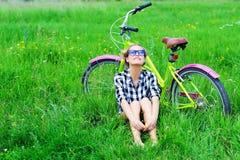 Vrij jonge meisjeszitting naast fiets in gras Royalty-vrije Stock Foto