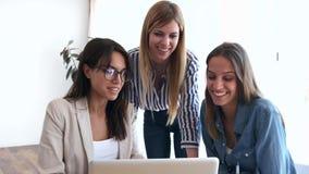 Vrij jonge onderneemster die vooruitgang van het werk aangaande laptop toont aan medewerkers in het bureau stock videobeelden