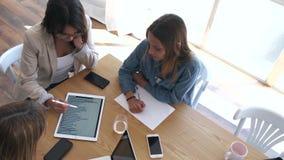 Vrij jonge onderneemster die vooruitgang van het werk in digitale tablet tonen aan medewerkers in het bureau stock video