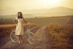 Vrij jonge smilling vrouw met retro fiets in zonsondergang op de weg, uitstekende oude tijden, meisje in retro stijl op weide stock fotografie
