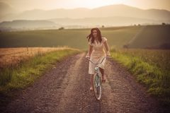 Vrij jonge smilling vrouw met retro fiets in zonsondergang op de weg, uitstekende oude tijden, meisje in retro stijl op weide royalty-vrije stock fotografie