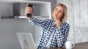 Vrij jonge toevallige glimlachende vrouw die selfie gebruikend smartphone bij moderne huiskeuken nemen stock video