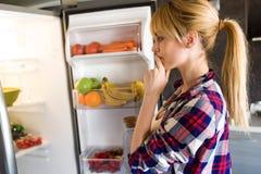 Vrij jonge vrouw aarzelend om voor de koelkast in de keuken te eten stock afbeelding