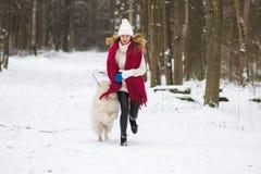 Vrij Jonge Vrouw in de Sneeuwwinter Forest Park Walking Playing met haar Hond royalty-vrije stock afbeeldingen