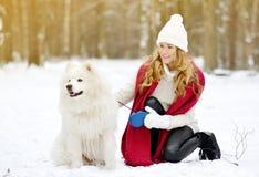 Vrij Jonge Vrouw in de Sneeuwwinter Forest Walking met haar Hond Witte Samoyed royalty-vrije stock fotografie