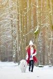 Vrij Jonge Vrouw in de Winter Forest Park Walking met haar Hond Witte Samoyed stock afbeelding