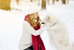 Vrij Jonge Vrouw in de Winter Forest Park Walking met haar Hond Witte Samoyed stock afbeeldingen