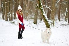 Vrij Jonge Vrouw in de Winter Forest Walking met haar Hond Witte Samoyed stock foto