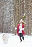 Vrij Jonge Vrouw in de Winter Forest Walking met haar Hond Witte Samoyed royalty-vrije stock afbeeldingen