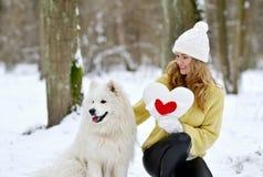 Vrij Jonge Vrouw in de Winter Sneeuwforest park walking met haar Hond stock fotografie