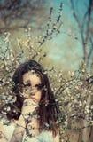 Vrij jonge vrouw dichtbij boom met bloemen stock foto's