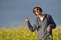 Vrij jonge vrouw die aan muziek in oortelefoons in in openlucht luisteren Royalty-vrije Stock Afbeelding