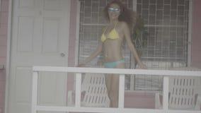 Vrij jonge vrouw die bikini dragen die en op het terras van roze huis glimlachen lopen stock footage