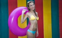 Vrij jonge vrouw die bikini dragen die roze opblaasbare ring op de kleurrijke muur houden royalty-vrije stock afbeeldingen