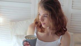 Vrij jonge vrouw die een kop van hete koffie met heemst houden stock video