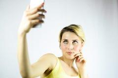 Vrij jonge vrouw die een selfie met een witte smartphone nemen Nadruk op het meisje Royalty-vrije Stock Afbeelding