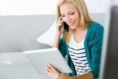 Vrij jonge vrouw die en haar mobiele telefoon werken met behulp van Royalty-vrije Stock Foto's