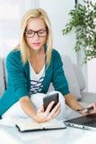 Vrij jonge vrouw die en haar mobiele telefoon werken met behulp van Royalty-vrije Stock Foto