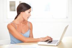 Vrij jonge vrouw die geschokt terwijl het bestuderen kijken stock afbeeldingen
