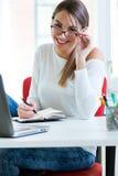Vrij jonge vrouw die in haar bureau werkt Stock Foto's