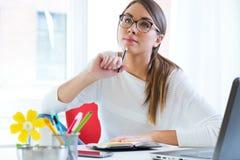 Vrij jonge vrouw die in haar bureau werkt Royalty-vrije Stock Foto