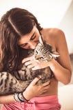 Vrij jonge vrouw die haar gestreepte katkat kussen bij de zomer royalty-vrije stock afbeelding