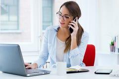 Vrij jonge vrouw die haar laptop in het bureau met behulp van Royalty-vrije Stock Afbeeldingen