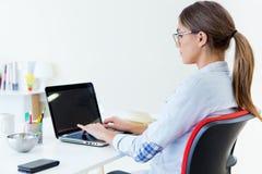Vrij jonge vrouw die haar laptop in het bureau met behulp van Royalty-vrije Stock Afbeelding