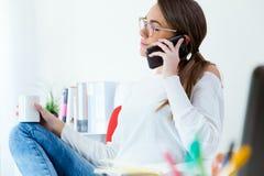 Vrij jonge vrouw die haar mobiele telefoon in het bureau met behulp van Stock Afbeelding