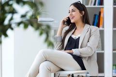 Vrij jonge vrouw die haar mobiele telefoon in het bureau met behulp van stock afbeeldingen