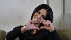 Vrij jonge vrouw die hart maken met handen ondertekenen stock afbeelding