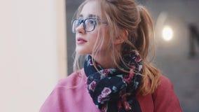 Vrij jonge vrouw die het zakboek in cafetaria, toen het dromerige kijken in het venster lezen Romantische modieuze uitrusting stock videobeelden