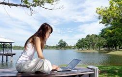 Vrij jonge vrouw die Internet in openlucht surft Stock Fotografie