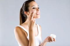 Vrij jonge vrouw die lichaamscrème toepassen Geïsoleerd op Gray Backgro stock fotografie