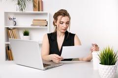 Vrij jonge vrouw die met documenten werken die voor haar computer zitten royalty-vrije stock foto