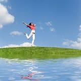 Mooie vrouw die op groen gras springen Royalty-vrije Stock Afbeeldingen