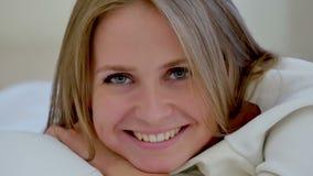 Vrij jonge vrouw die op haar bed liggen die bij camera glimlachen stock videobeelden