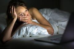Vrij jonge vrouw die op iets letten vreselijk/droevig op haar laptop Stock Fotografie
