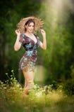 Vrij jonge vrouw die strohoed het stellen in bos dragen Royalty-vrije Stock Foto's
