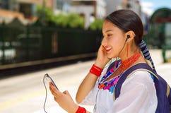 Vrij jonge vrouw die traditionele Andesblouse en blauwe rugzak dragen, die op bus bij in openlucht postplatform wachten Stock Foto